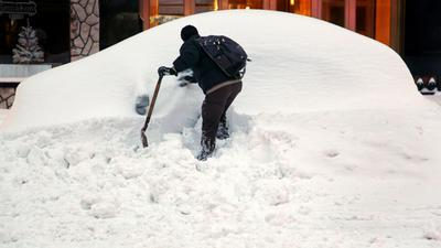 John Elliot of New York tries to dig out his rental car on a Manhattan street Monday, thanks in part to a good Samaritan who let him use a shovel. (AP)