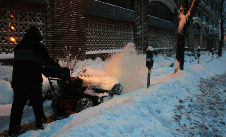 A man clears a sidewalk in front of an apartment building in Brookline. (Jeremy Bernfeld for WBUR)
