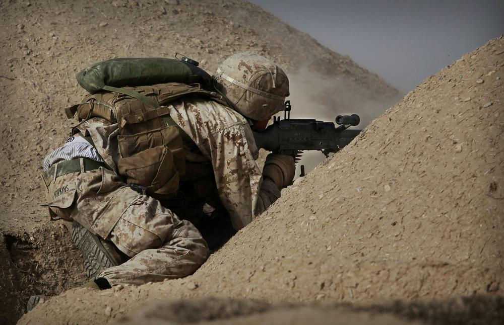 United States Marine Cpl. Jesse Hopkins from Bravo Company of the 1st Battalion of the 2nd Marines fires a machine gun during a gun battle as part of an operation to clear the area of insurgents near Musa Qaleh, in northern Helmand Province, southern Afghanistan in 2010. (AP)