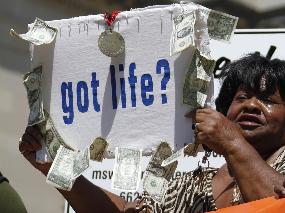 Civil rights activist Dorothy Benford of Jackson, waves a sign with $11 in singles hanging from it to protest the life sentences Jamie and Gladys Scott received for a robbery that netted that same amount, during a rally at the Capitol in Jackson, Miss., in September. (AP)
