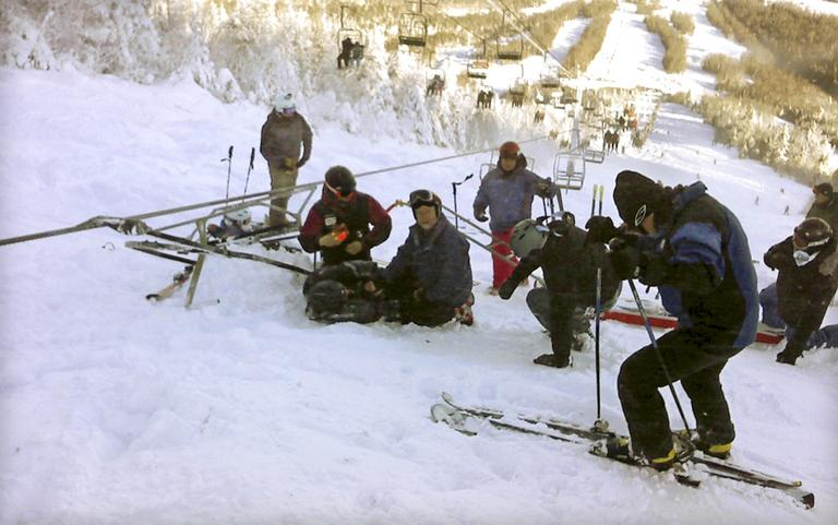 Skiers attending a skier who fell onto the slope after a chair lift derailed on the state's tallest ski mountain at the Sugarloaf resort in Carrabassett Valley, Maine, Tuesday, Dec. 28, 2010. (AP)