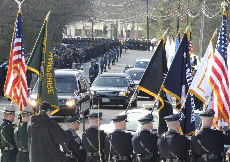 Police stood guard at the memorial service for Woburn Police Officer Jack Maquire in Wilmington, Friday. (AP)