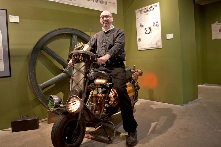 Bruce Rosenbaum, owner of Steampuffin and ModVic, sits on top of a steampunked scooter.(Nicholas Dynan for WBUR)