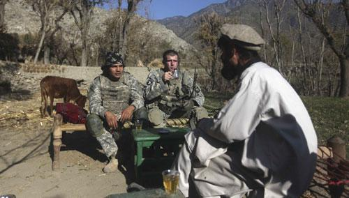 U.S. servicemen drink tea with an Afghan man near the Pakistani border in Kunar province, eastern Afghanistan, Dec 20, 2010. (AP)