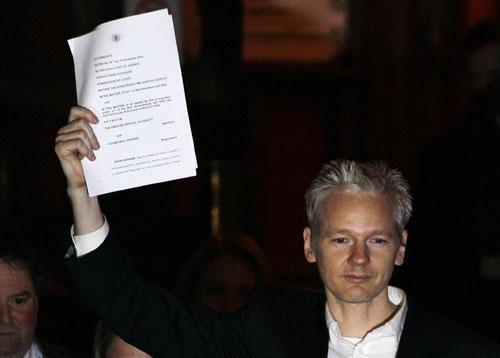 WikiLeaks founder Julian Assange holds up a court document after he was released on bail, outside the High Court, London, Dec. 16, 2010. (AP)