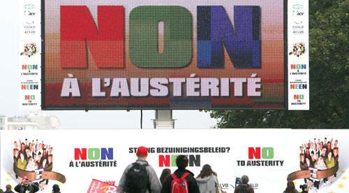 Protestors walk past a billboard which reads 'No to austerity' during a demonstration in Brussels, 2010. (AP)