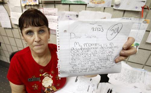 "U. S. Postal Service employee Rita Rose displays one of thousands of ""Dear Santa"" letters that her office handles in Sacramento, Calif., Dec. 15, 2010. (AP)"