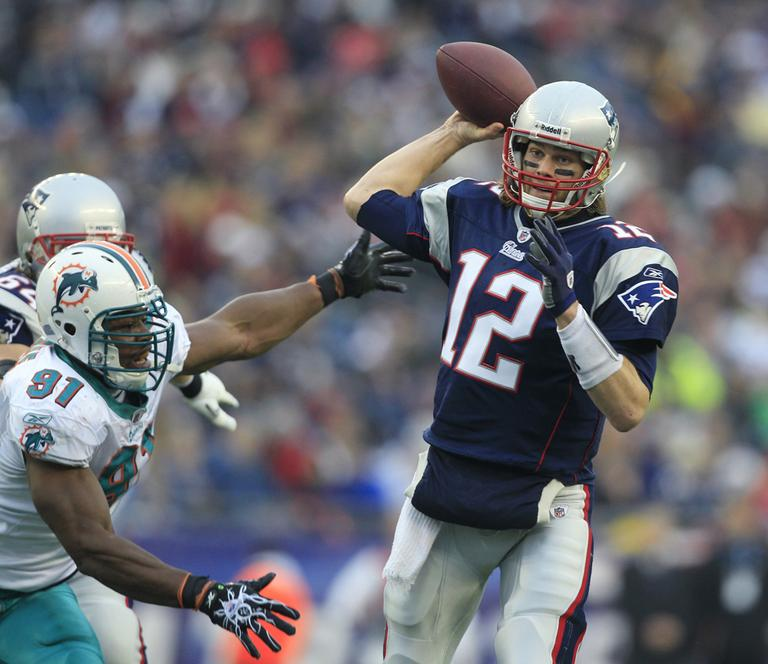 New England quarterback Tom Brady sets to throw as Miami linebacker Cameron Wake pressures him during the second quarter of the game in Foxborough on Sunday. (AP)