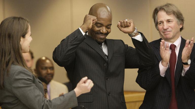 Cornelius Dupree Jr., center, raises his hands in celebration with his lawyer Nina Morrison, left, and attorney Barry Scheck in Dallas on Tuesday, Jan. 4, 2010. (AP)
