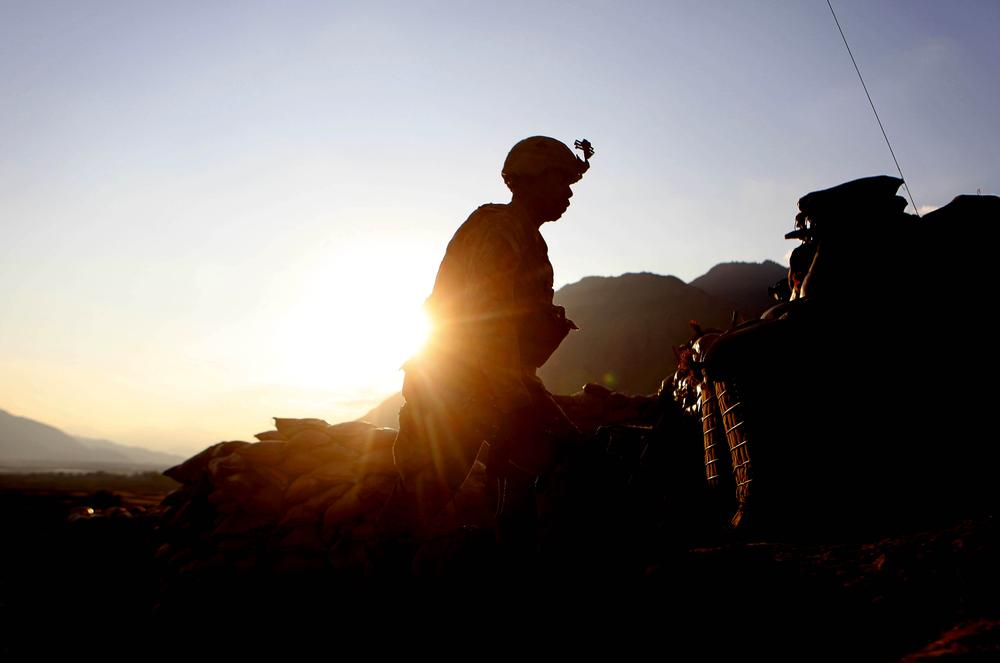 Pfc. Robinson Chaz of the 2nd Platoon Bravo Company 2-327 Infantry walks at sunset at Badel Combat Out Post in Kunar province in eastern Afghanistan near the Pakistan border. (AP)