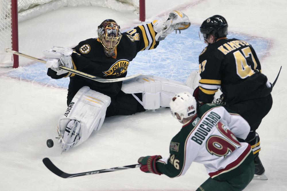 Boston goalie Tuukka Rask, of Finland, left, drops to the ice to make a save as Minnesota center Pierre-Marc Bouchard (96) looks for the rebound during the first period of the game on Thursday in Boston. At top right is Bruins defenseman Steve Kampfer. (AP)