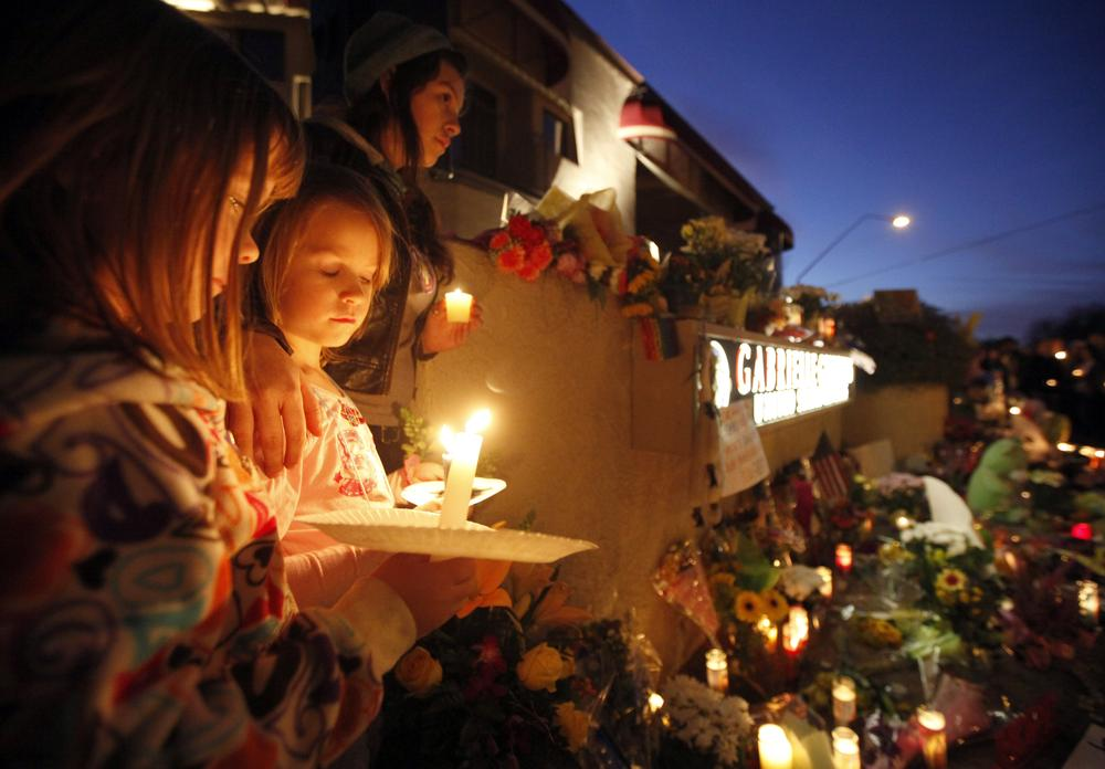 From left, Ellie Steve, 6, Lucia Reeves, 6, and Zoe Reeves, 18, gather for a candlelight vigil outside the offices U.S. Rep. Gabrielle Giffords, D-Ariz., in Tucson, Ariz. (AP)