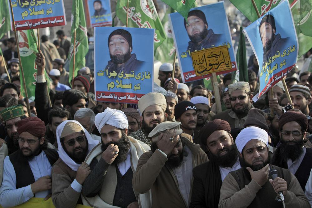Supporters of Pakistani religious party Sunni Tehreek raise posters showing Mumtaz Qadri, alleged killer of Punjab governor Salman Taseer, during a rally supporting him and calling his release in Rawalpindi, Pakistan. (AP)