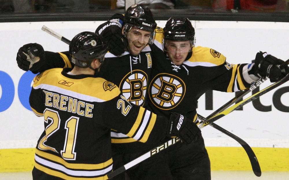 Boston center Patrice Bergeron, center, is congratulated by teammates Andrew Ference, left, and Brad Marchand, right, after scoring the third goal of his hat trick against Ottawa during the third period of an NHL hockey game in Boston on Tuesday. (AP)
