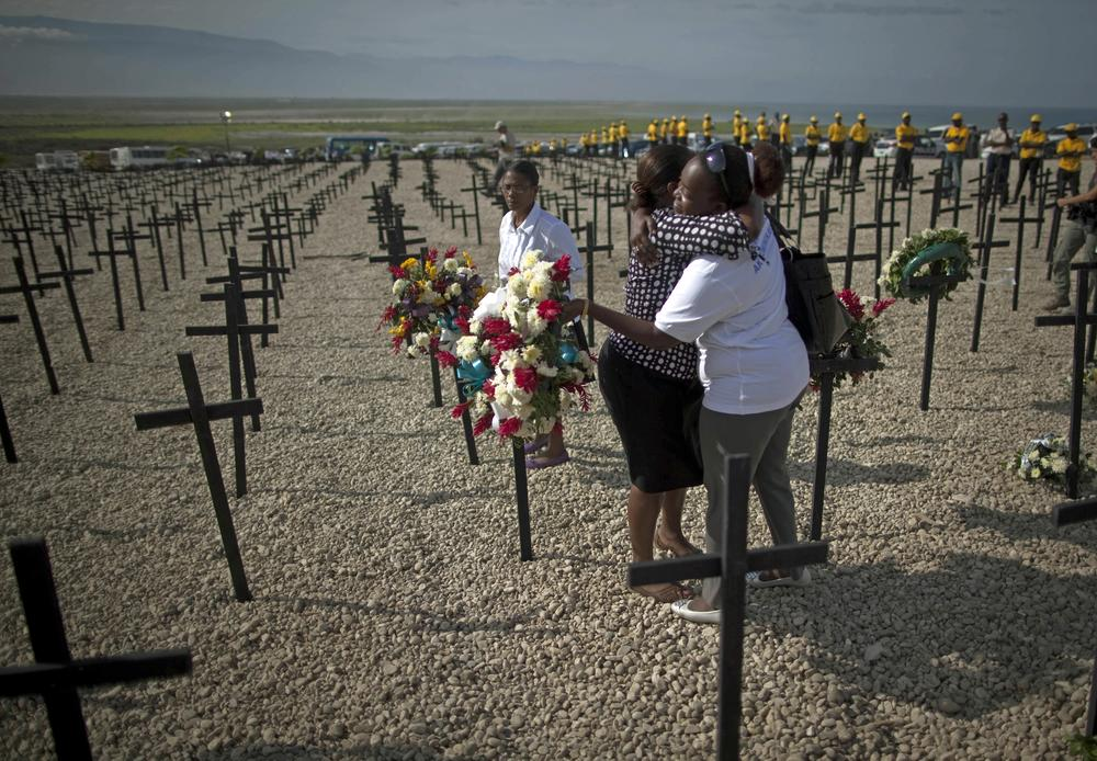 Two women embrace during a religious ceremony held at the Titanyen mass grave site on the outskirts of Port-au-Prince, Haiti. (AP)
