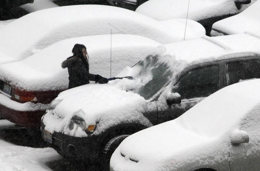 A woman clears fresh snow from her car in downtown Cleveland, Ohio parking lot. (AP)