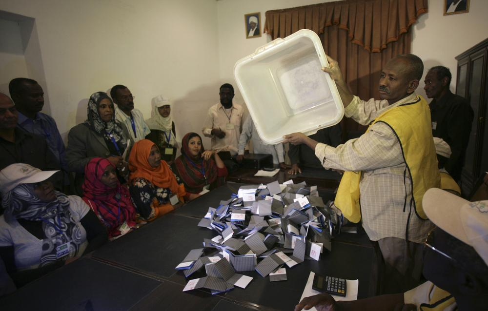 A polling staff member empties a ballot box at the end of a weeklong voting process, at a polling center in Khartoum, Sudan. (AP)