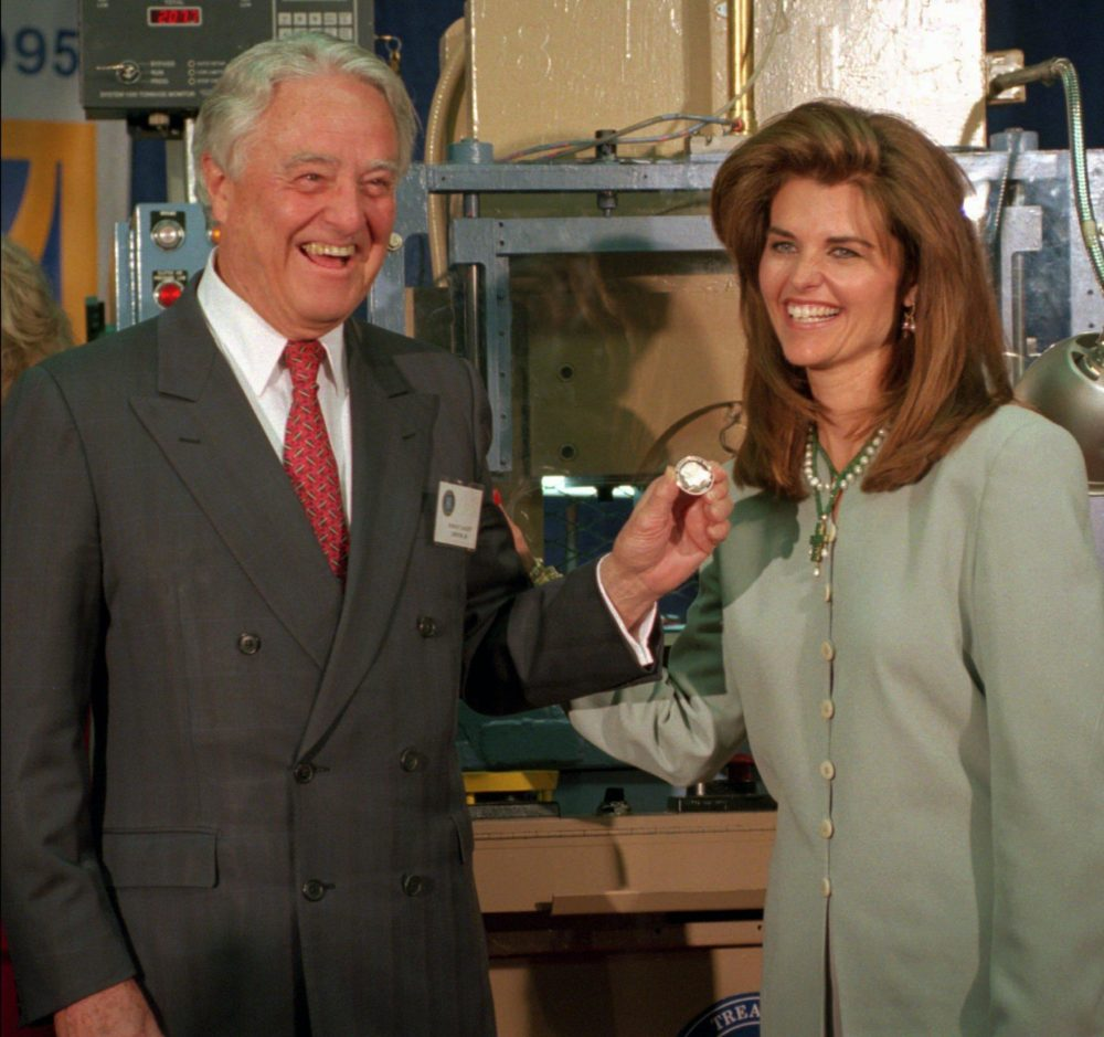 R. Sargent Shriver and his daughter, Maria, hold a newly minted commemorative silver dollar coin honoring his wife, Eunice Kennedy Shriver, at the U.S. Mint in Philadelphia, in 1995. (AP)