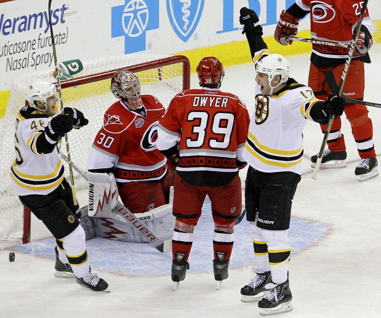 Boston's Milan Lucic (17) and David Krejci, left, of the Czech Republic, celebrate Lucic's goal against Carolina goalie Cam Ward (30) as Patrick Dwyer (39) looks on during the third period of the game in Raleigh, N.C., on Tuesday. Boston won 3-2. (AP)