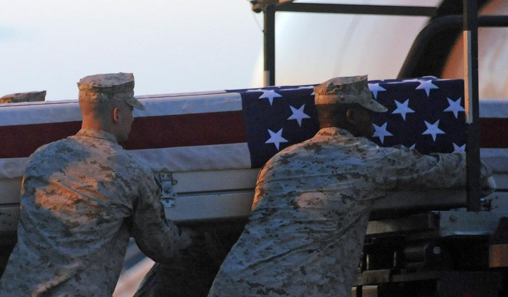 A Marine carry team lifts a transfer case containing the remains of Cpl. Paul J. Miller at Dover Air Force Base, Del., July 21, 2010. (Steve Ruark/AP)