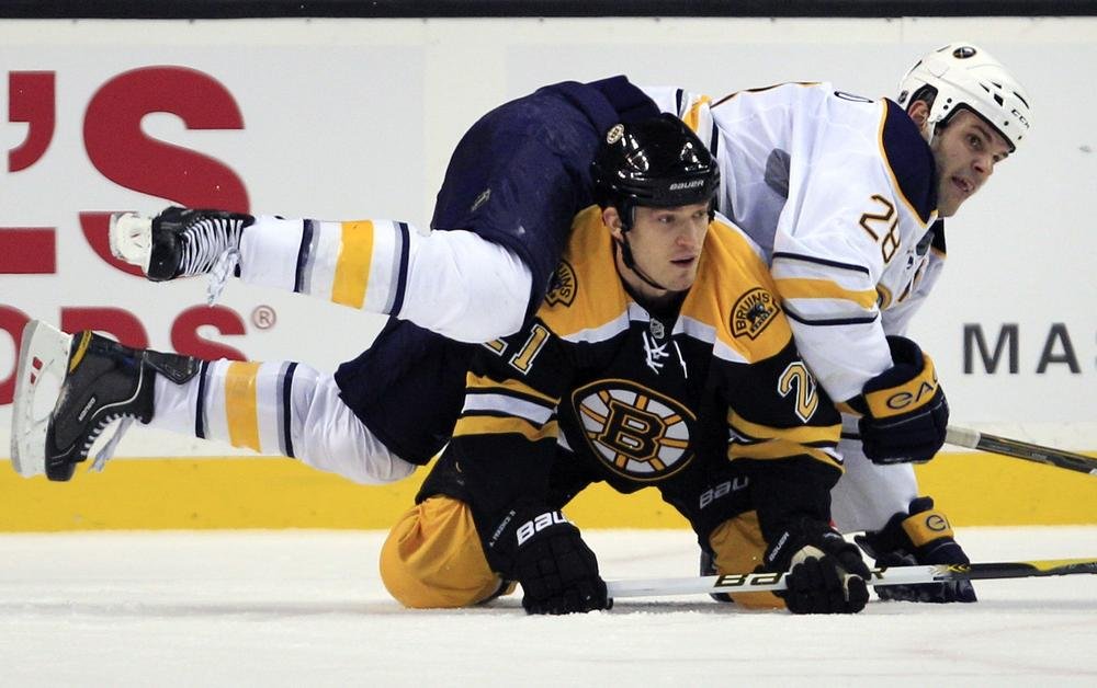 Buffalo center Paul Gaustad, top, lands on Boston defenseman Andrew Ference while chasing the puck during the second period of the game in Boston on Thursday. (AP)