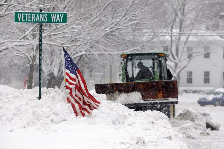 A bucket loader moves snow off the town square in Norwell on Friday. (AP)