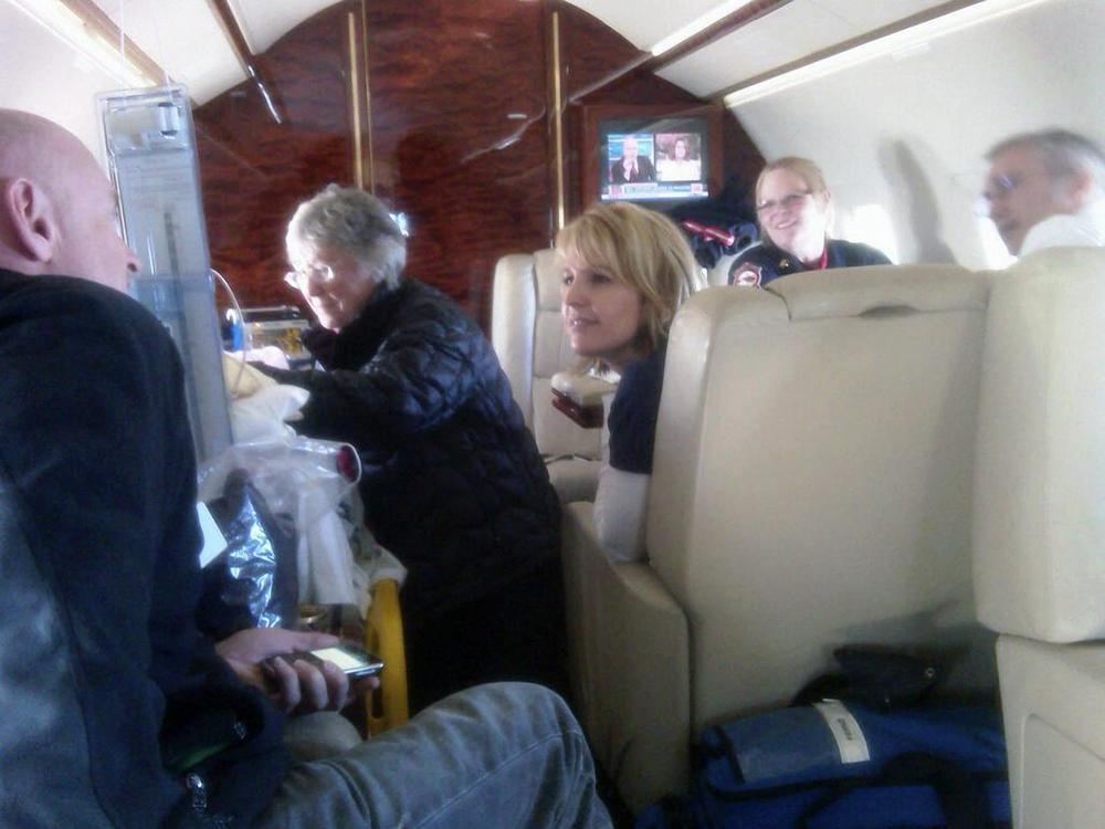 In this Friday, Jan. 21, 2011 photo released by the office of Rep. Gabrielle Giffords, D-Ariz., Gloria Giffords, the congresswoman's mother, center, talks with her daughter aboard the plane transporting her from Tucson to Houston. The congresswoman's husband, Capt. Mark Kelly, far left. talks with  Tracy Culbert, one of Congresswoman Giffords' nurses in UMC's intensive care unit. (AP Photo/Congresswoman Giffords' Office)