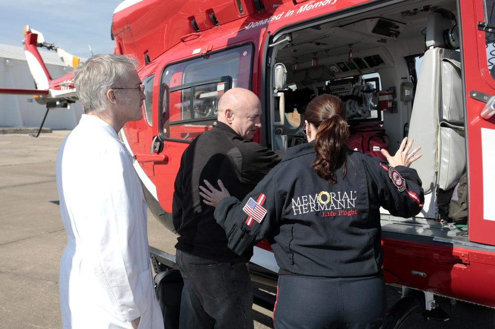 The husband of Rep. Gabrielle Giffords, D-Ariz, Mark Kelly, center, prepares to climb into a helicopter in Houston. Giffords, who is recovering from a gunshot wound to the head was transferred to a Houston intensive care unit. (AP/Office of Rep. Giffords, F. Carter Smith)