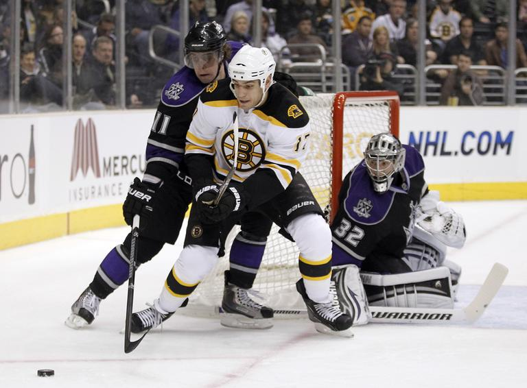 Los Angeles center Anze Kopitar, left, reaches for the puck next to Boston left wing Milan Lucic, as Kings goalie Jonathan Quick looks on during the first period of the game in Los Angeles on Monday. (AP)