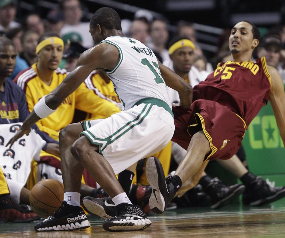 Cleveland center Ryan Hollins (5) falls to the floor as Boston forward Glen Davis (11) tries to move the ball during the second half of the game at the Garden in Boston on Tuesday. Davis was called for charging. The Celtics defeated the Cavaliers 112-95. (AP)