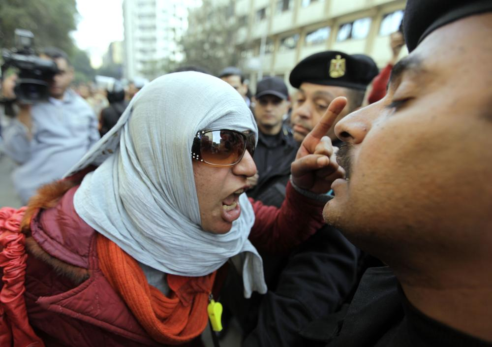 An Egyptian activist shouts at anti-riot policemen who block the way leading to journalists syndicate in downtown Cairo, Egypt. (AP)