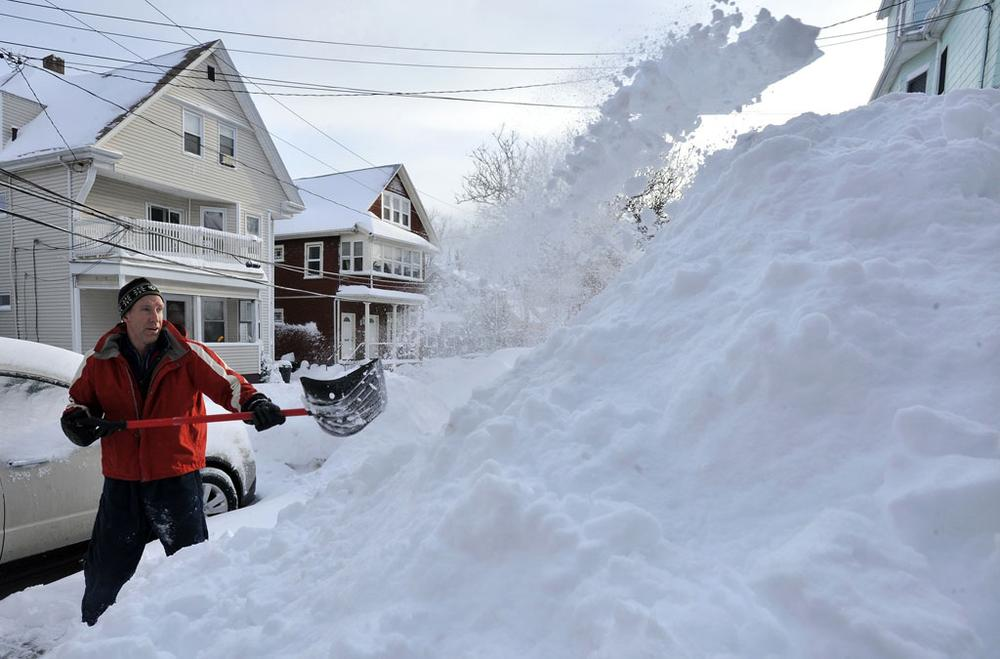 Kevin Andrew adds to the pile of snow on his front yard as he clears his driveway in Somerville on Thursday. (AP)