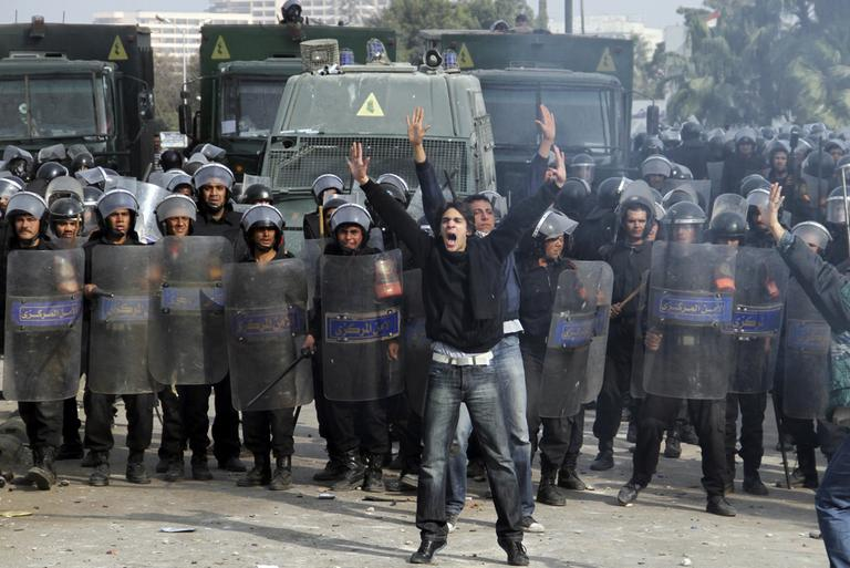 Egyptian protesters shout in front of anti-riot policemen who block a bridge in Cairo, Egypt, Friday. (AP)