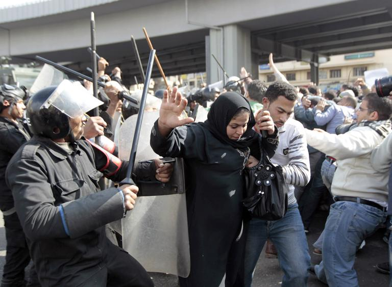 An Egyptian woman flees as Egyptian anti-riot policemen clash with protesters in Cairo, Egypt, Friday, Jan. 28, 2011. (AP)
