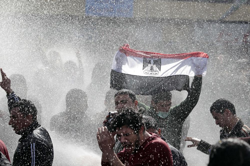 An Egyptian protester flashes Egypt's flag as anti-riot policemen use water canon against protesters in Cairo, Egypt. (AP)