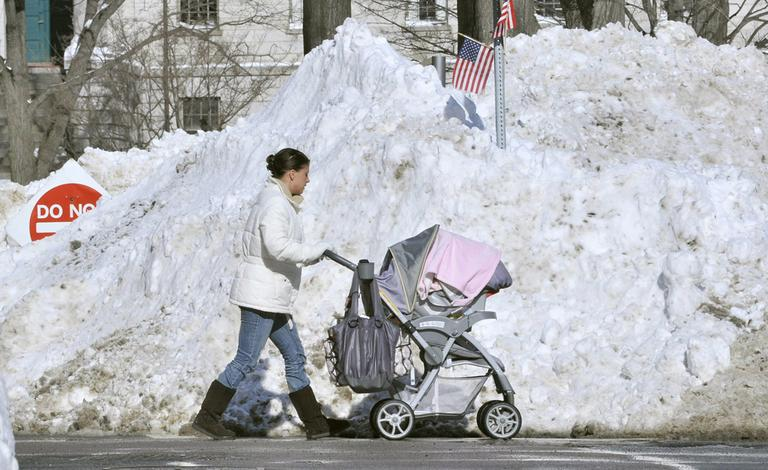 A pedestrian, forced into the street by blocked sidewalks, passes piles of snow outside Massachusetts General Hospital in Boston on Thursday. (AP)