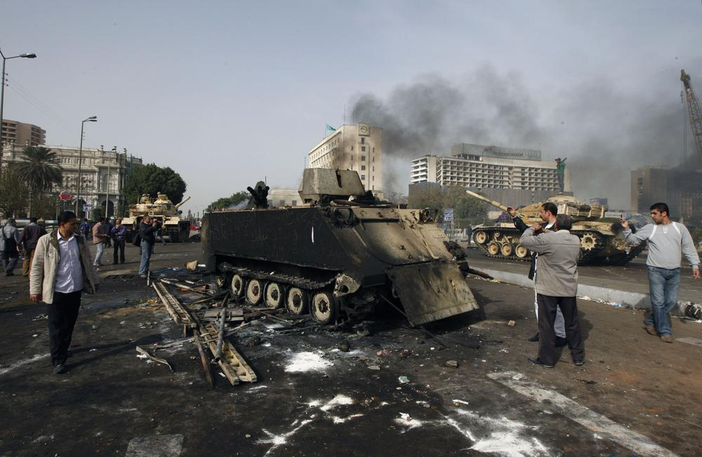 Egyptians photograph a burned out army armored personnel carrier in downtown Cairo, Egypt, Saturday, Jan. 29, 2011. (AP Photo/Khalil Hamra)