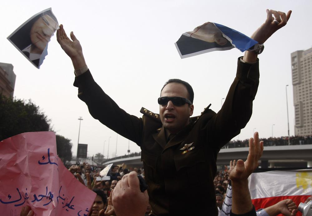 An army officer who joined anti-government protester tears up a picture of Egyptian President Hosni Mubarak, downtown Cairo, Egypt, Saturday, Jan. 29, 2011. (AP Photo/Ahmed Gumaa)