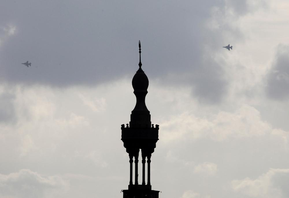 Military fighter jets are seen behind the minaret of the Aguza mosque in Cairo, Sunday, Jan. 30, 2011. (AP Photo/Manoocher Deghati)