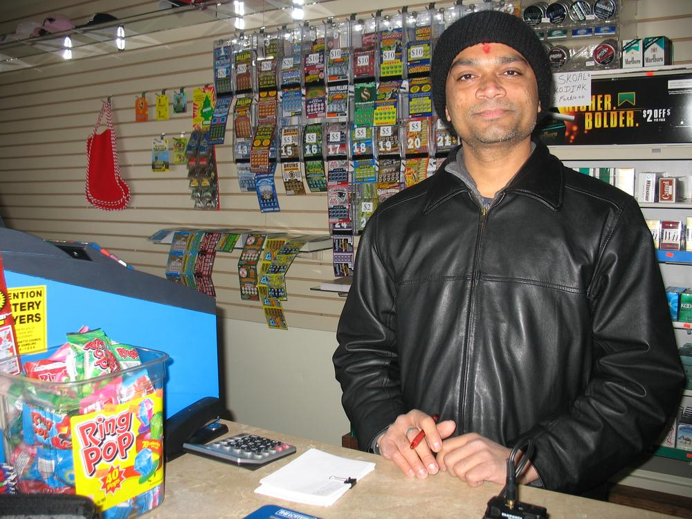 Vinny Patel opened his convenience store Wednesday, even though it had no power. (Martha Bebinger/WBUR)