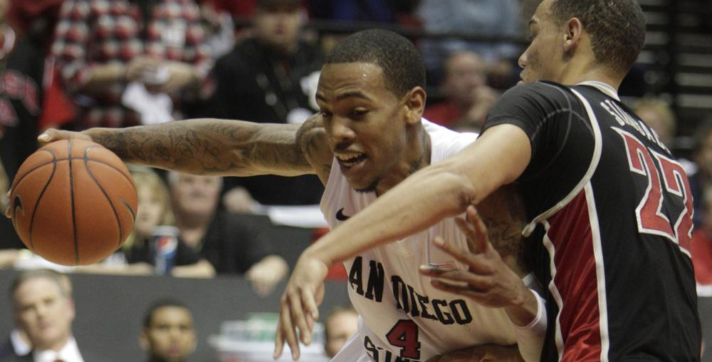 San Diego State's Malcolm Thomas lowers his shoulder into UNLV's Chace Stanback. (AP Photo/Lenny Ignelzi)