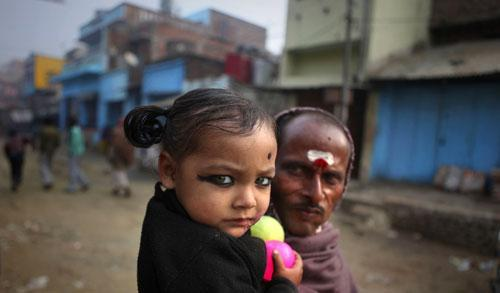 A young Indian girl looks on with her father, in their village, Kosi, some 180 kilometers from Patna, India, Jan. 24, 2011. (AP)