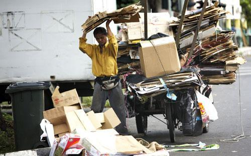 An unemployed man in Singapore collects cardboard waste to exchange for money along a residential area, Jan. 5, 2011. (AP)