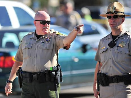 A sheriff speaks to another officer at the scene of the shooting in Tucson, Ariz. on Saturday. (AP)