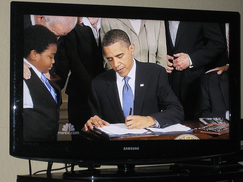 President Obama signing the health care bill into law