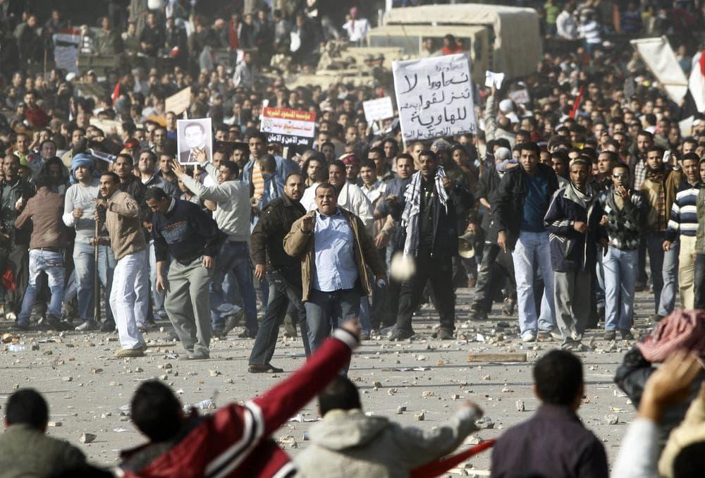 Pro-government supporters, top, clash anti-government protestors in Cairo's main square, Egypt. (AP)