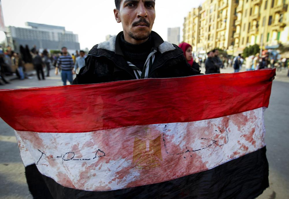 An anti-government protester displays an Egyptian flag, covered with blood, during clashes in Tahrir, or Liberation square, in Cairo, Egypt. (AP)