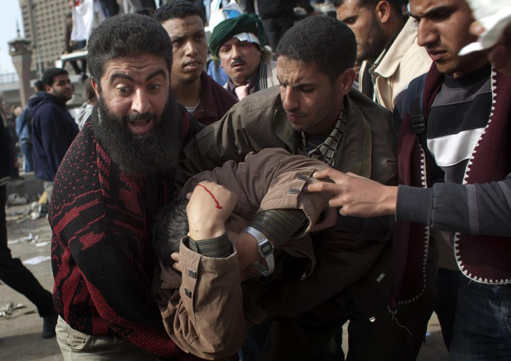 An anti-government protestor gets assistance after being wounded during clashes in Cairo, Egypt, Thursday. (AP)