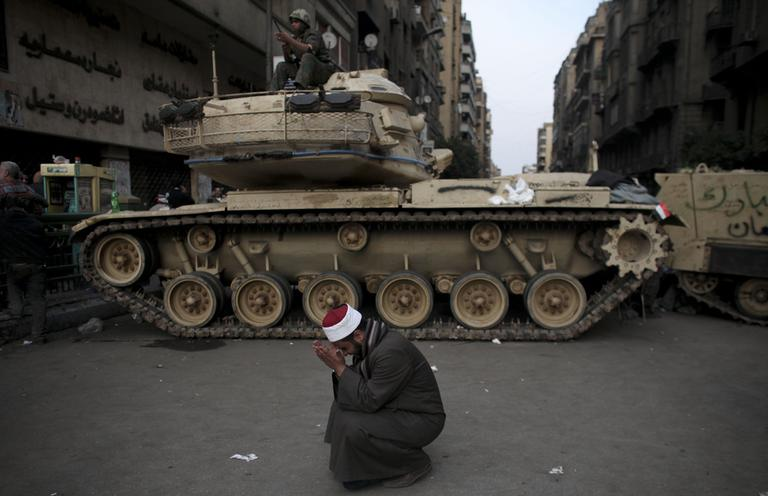 An Egyptian Muslim cleric weeps for slain protesters in front of on army tank in Tahrir square, in Cairo, Wednesday. (AP)
