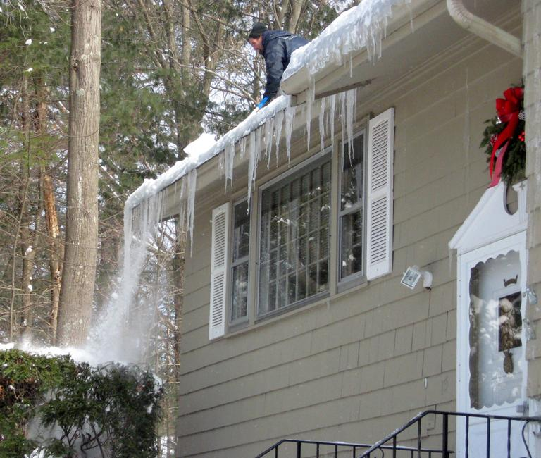A roofer clears out an ice dam that has formed atop a home in Acton. (David Boeri/WBUR)